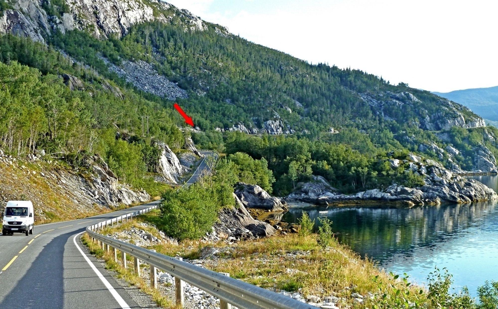 Den røde pilen markerer tunnelinnslaget i sørvest. Vegen langs fjellsiden i bakgrunnen blir stengt når tunnelen åpnes 12.12.1012.