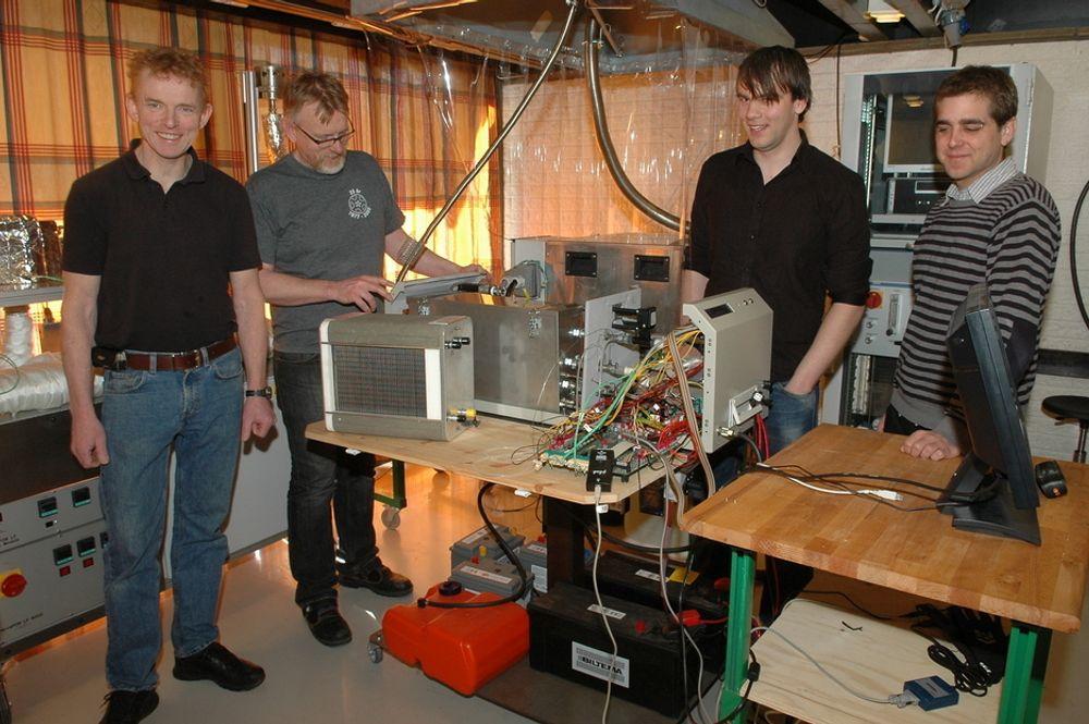 PILOT: Pilotaggregatet på 1 kW er snart klart. I forkant sees selve brenselcellen i grafitt. Pilotaggregatet skal senere til testing hos forsvaret. Fra venstre Dag Øvrebø, Tore Lie, Erlend K. Timberlid og Cameron Lindberg