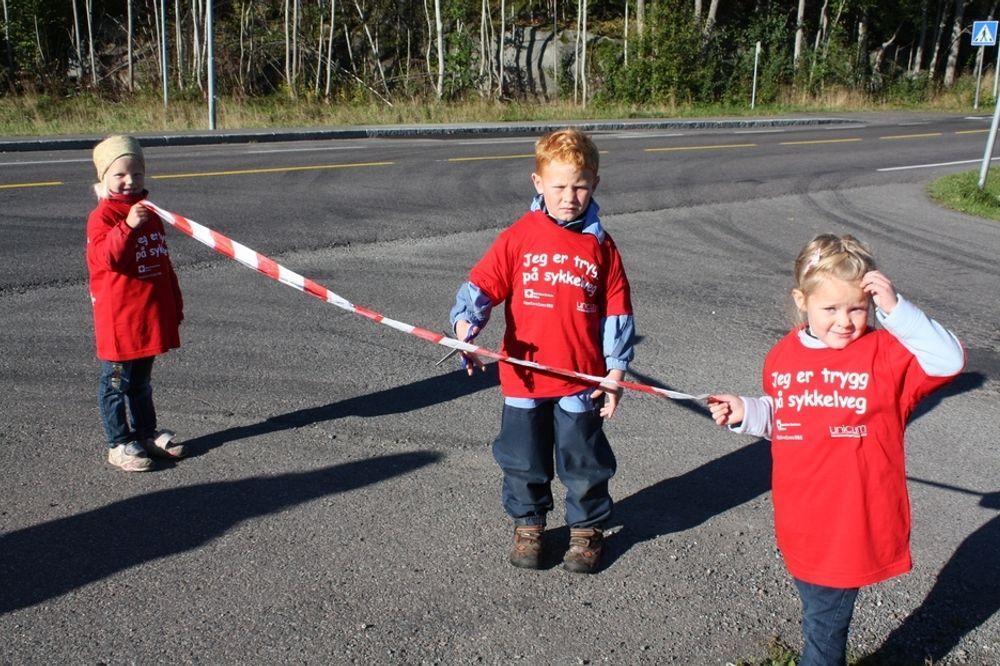 Emil Schøning-Olsen fra Lindhøy skole markerer at det er sammenhengende gang/sykkelveg langs fylkesveg 308 fra Tønsberg til Havnaveien. Eirin Østheim Pettersen (til venstre) og Sara Elisabeth Arnesen Silver holder snoren.
