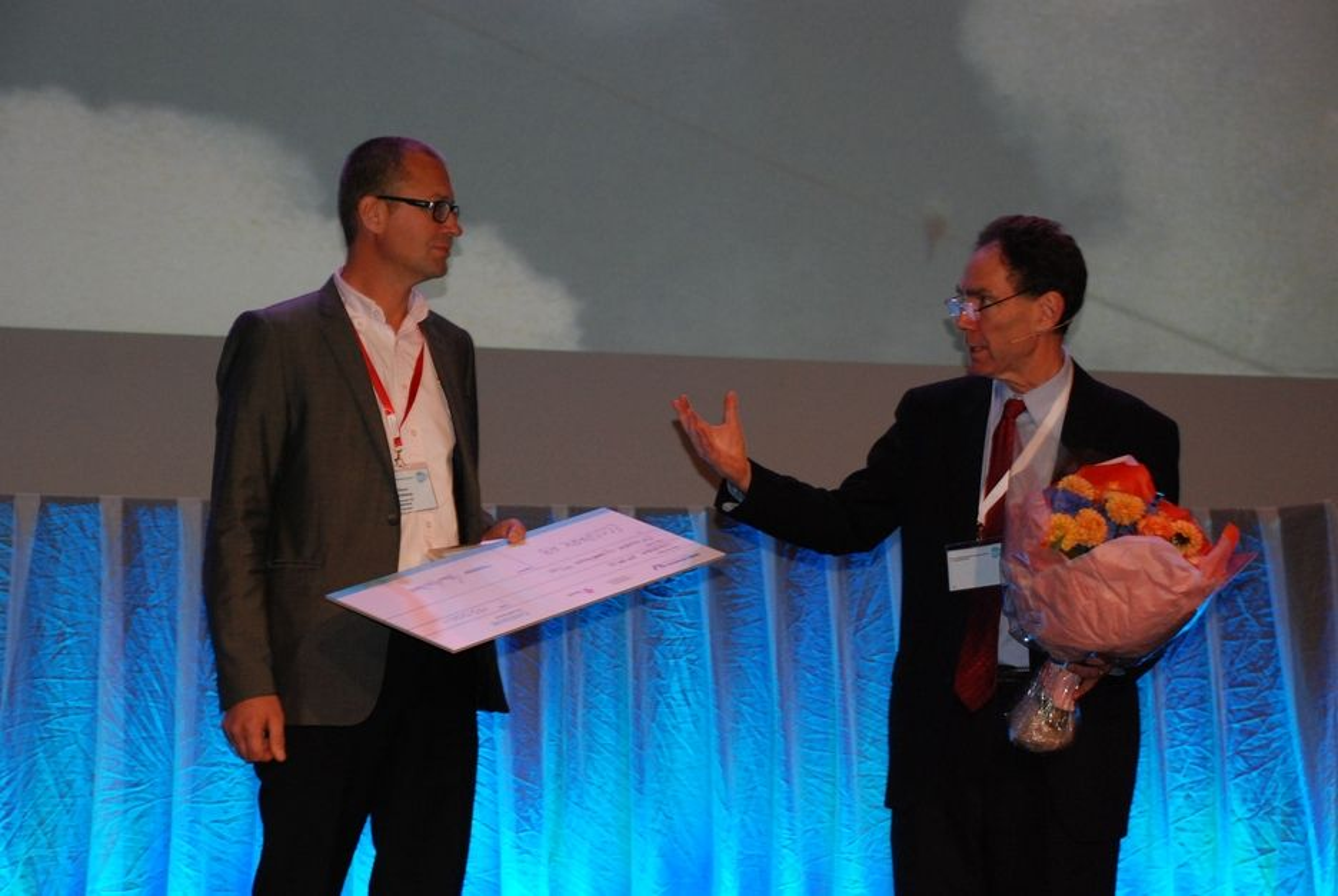 -  SE HVA VI HAR HER, EN SJEKK! Hans Lindberg i Eco Spark AB mottok Nerec Innovation Award, en sjekk på 150 000 kroner fra konferansier Todd Benjaminsen.