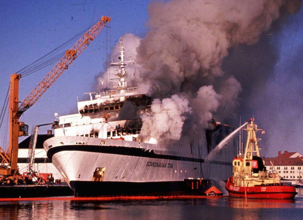 """TRAGEDIE: Det begynte å brenne om bord i passasjerferjen """"Scandinavian Star"""" i Skagerrak mellom Oslo og Fredrikshavn natt til 7. april 1990. 159 mennesker omkom. Her er skipet i brann ved kaia i Lysekil."""