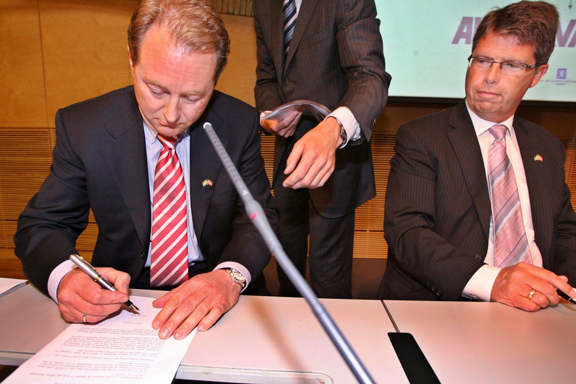 Staten går inn på eiersiden i Aker Kværner, sammen med Aker ASA, Investor AB og Saab AB, opplyste næringsminister Dag Terje Andersen på en pressekonferanse i juni. Her signerer Kjell Inge Røkke kontrakten mens administrerende direktør i Aker konsernet Leif Arne Langøy ser på.