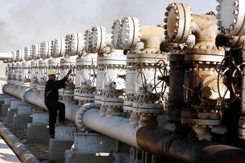 En arbeider justerer en ventil ved et oljeanlegg i det sørlige Irak. Norske StatoilHydro er blant selskapene som nå deltar i budrunden foran tildelingen av konsesjoner på utbygging av ti nye oljefelter, hvorav tre regnes blant de største i verden. Den to dager lange runden ble innledet i Bagdad fredag, og regnes som av stor betydning for det krigsherjede Iraks økonomi.