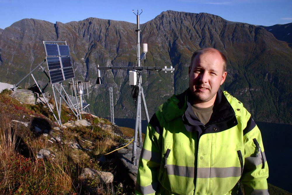 TRYGT: Dataingeniør Tore Bergnes i Åknes-Tafjord Beredskap IKS på toppen av Åkneset der det er montert avansert teknologisk utstyr som skal kunne varsle et ras fra Åkneset flere dager i forveien. Nå kan folk igjen bygge i området, mener regjeringen.