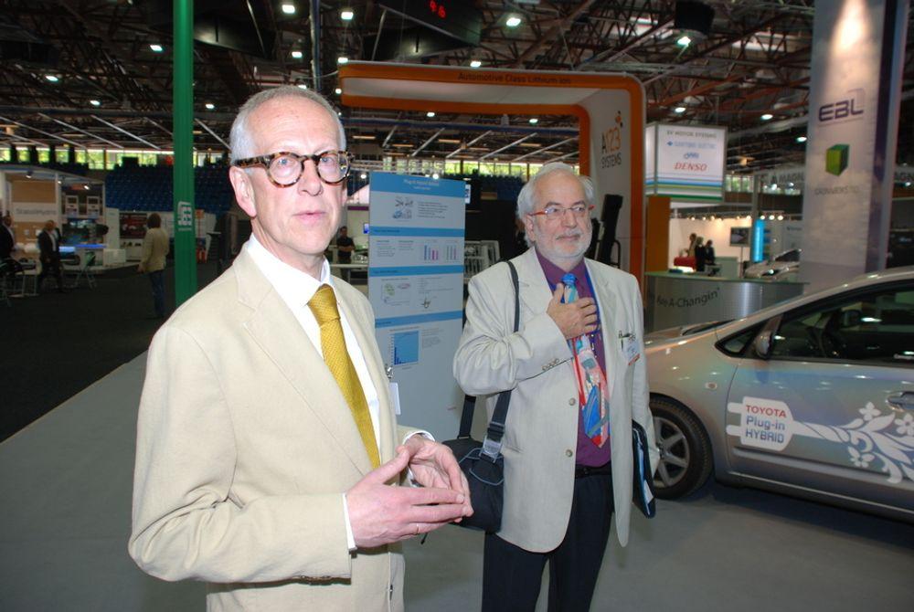 VISER RUNDT: Harald Røstvik og Robert Stüssi i organisasjonskomiteen for EVS24-symposiet viser pressen rundt på messeområdet før den offisielle visningen. Her ser de på en Toyota som er ombygd til å bli en ladbar hybridbil som går både på bensin og elektrisitet.