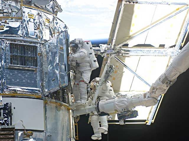Astronauts John Grunsfeld (left) and Richard Linnehan work to replace the Hubble Space Telescope's power control unit during the last Hubble servicing mission in March 2002. Courtesy NASA.