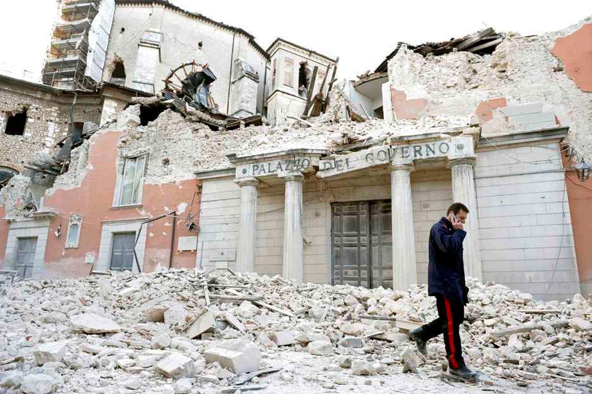RASERT: En italiensk politimann går forbi ett av husene som raste sammen under nattens jordskjelv. Mange er drept fordi husene deres raste sammen.