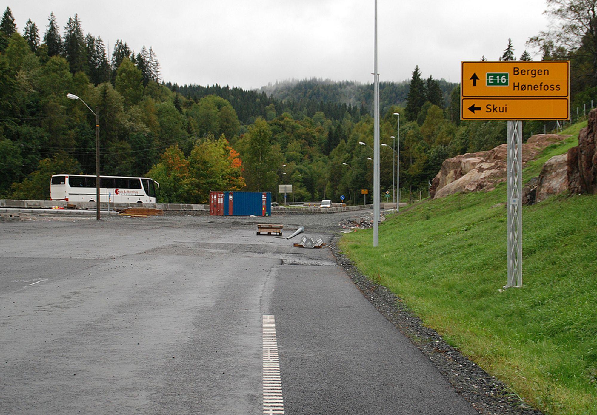 E16, Bærum kommune. Bildet tatt fra nye E16 i september 2008, der den ferdige parsellen Wøyen (Vøyenenga) - Bjørum skal kobles på dagens E16 våren 2009. Den nye veien er allerede ferdig oppmerket og skiltet, men trafikken går fortsatt langs den smale, svingete veien opp fra Skui.