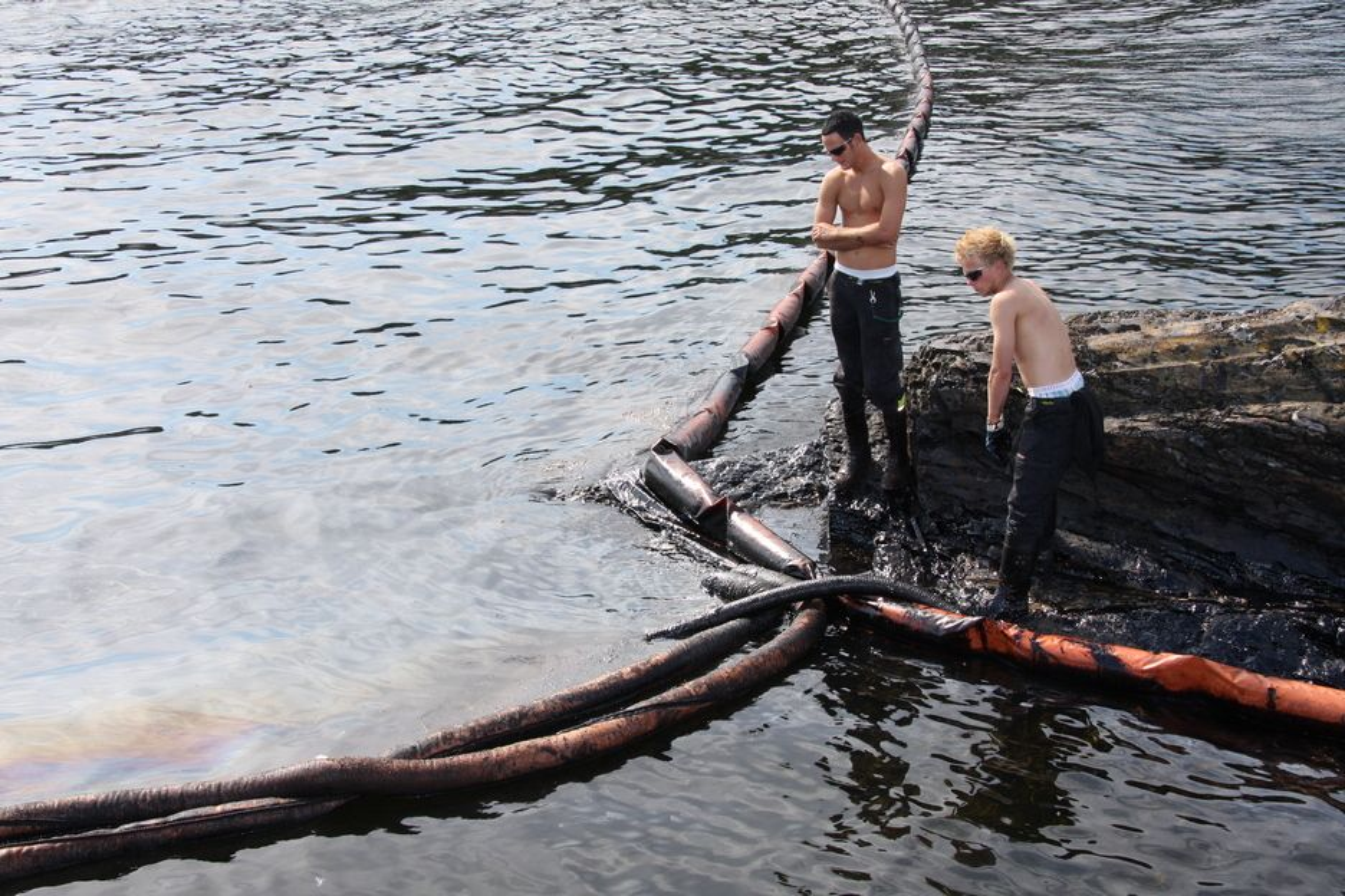 Mannskap fra Veolia Miljø suger opp olje i Krogshavn ved Langesund.