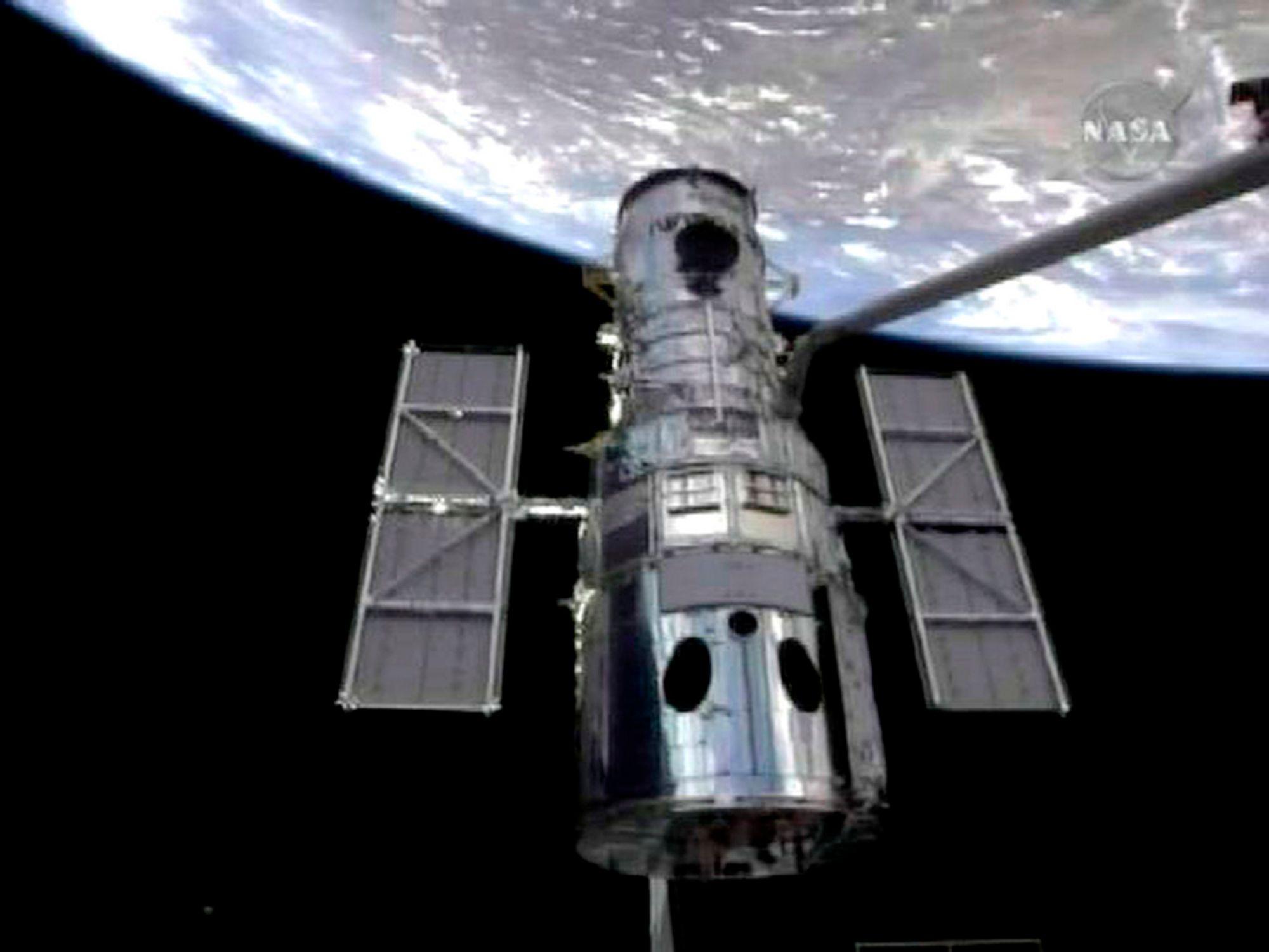 Robotarmen på romferja Atlantis grep onsdag om romteleskopet Hubble og trakk det med inn i romferjas lasterom for en omfattende overhaling.