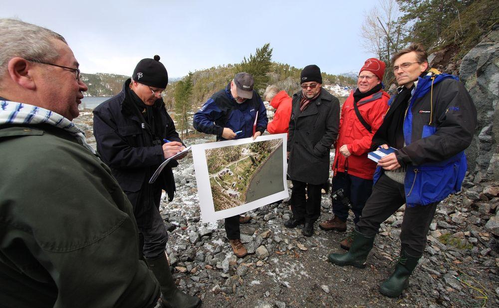 Svein Haugen (t.v) var en av dem med best utsikt til raset oppe fra huset sitt i skråninga som så vidt ble skjermet. Han fortalte at han tidlig i hendelsen så en 15-20 meter høy vannsøyle sprute opp nede ved vegen, noe som tyder på at vannledningen var truffet. Her forteller han om sine opplevelser til ekspertgruppa, fra høyre: professor Steinar Nordal ved NTNU som leder gruppa, Dr. Christian Madshus, NGI, professor Claes Alén, Chalmers Tekniska Høgskola, dosent Leif Jendeby, Vägverket, siv.ing. Einar Lyche, Rambøl og amansuensis Arfinn Emdal ved NTNU som bistår Nordal men ikke formelt er en del av granskningsutvalget.