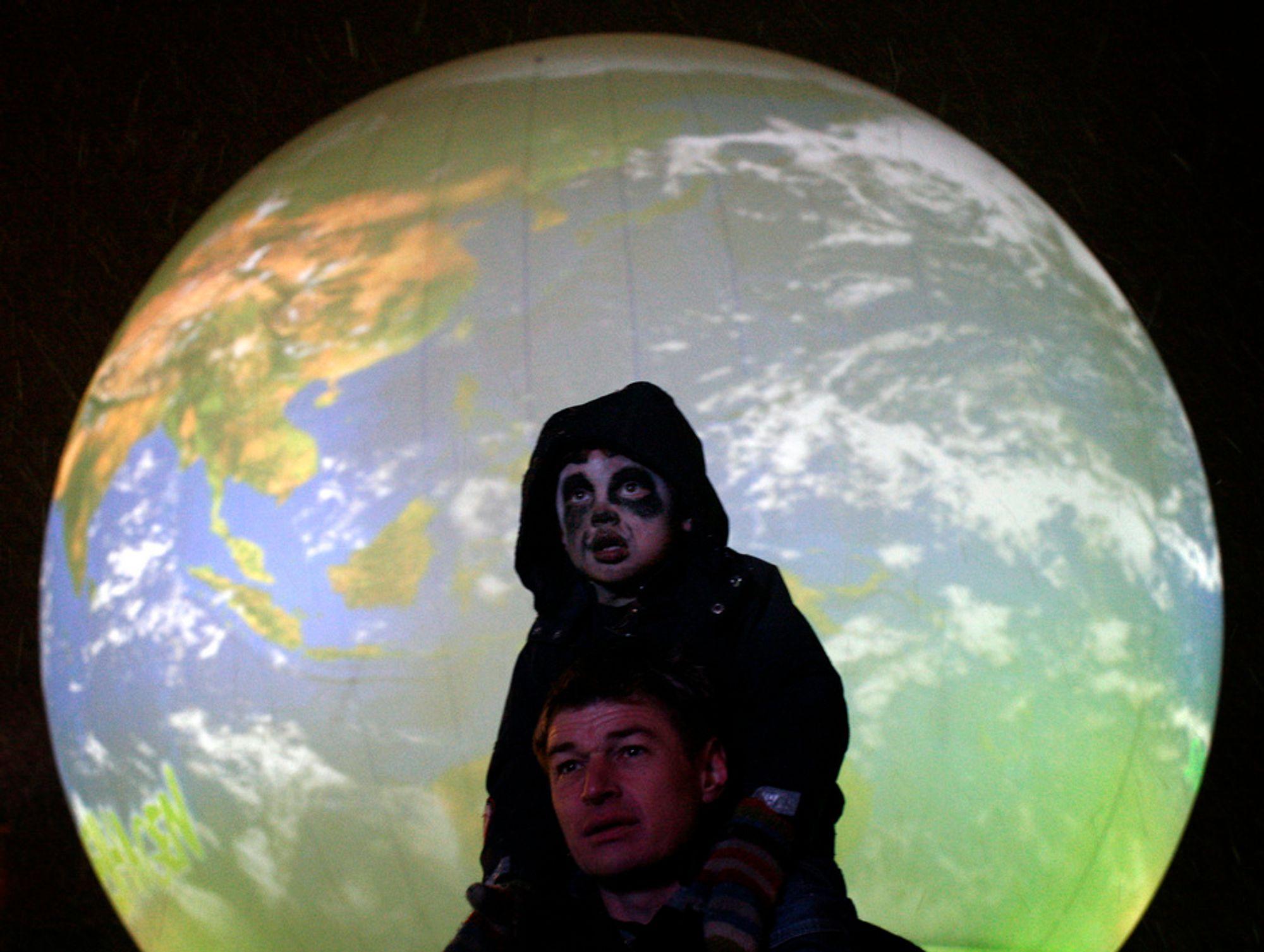 En gutt sitter på sin fars skuldre på Rådhusplassen i København under en markering for en klimaavtale. Håpet svinner om utsiktene til at det blir en avtale på klimatoppmøte
