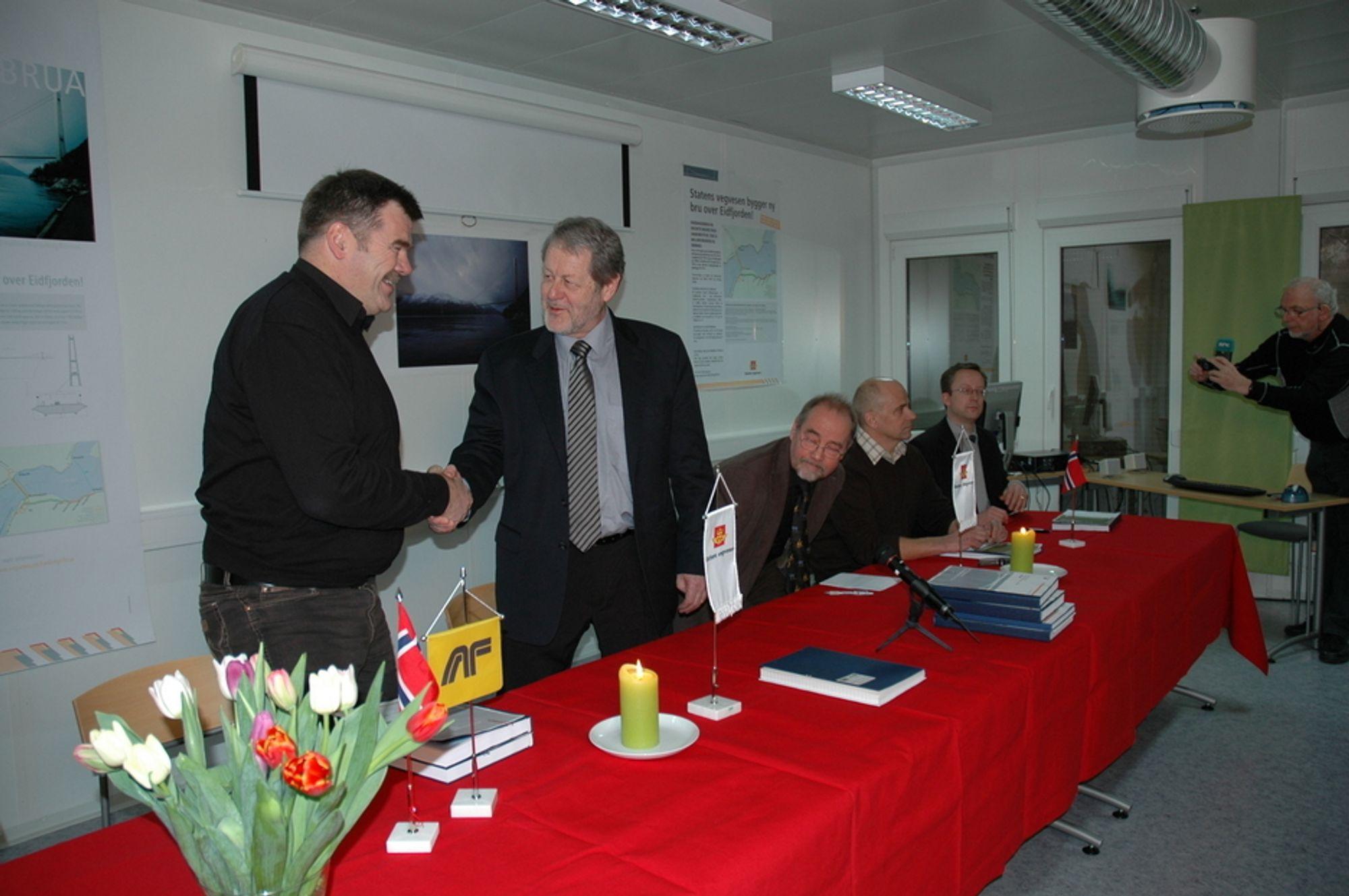Robert Haugen i AF Gruppen (t.v.) gratuleres av regionveisjef Olav Ellevset. Videre fra venstre sitter prosjektleder Øivind Søvik, Klaus Hansen fra Veidekke og Christian Levinsen fra MT Højgaard.