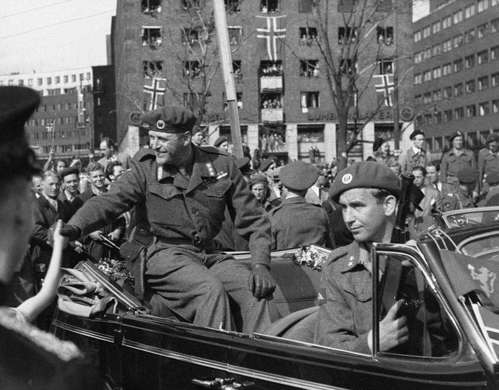 VAR OGSÅ LIVVAKT: Du har sikkert sett dette kjente bildet av Kong Olav i åpen bil i Oslos gater da han kom tilbake til Norge etter krigen. Ved siden av sitter krigshelten Max Manus med et skrapladd våpen. Sammen med Oslogjengen var Max rett etter krigen vakt for hele kongefamilien.