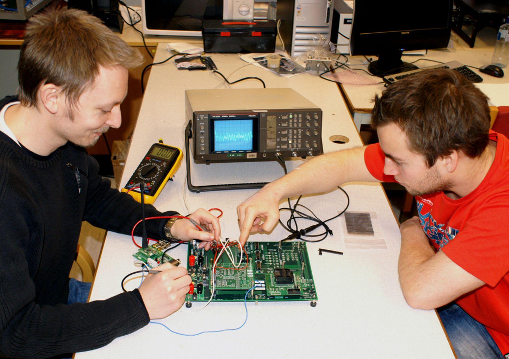 Romteknologistudentene Espen Oland (til høyre) og Lasse Ulvær jobber med testbrettet til Høgskolen i Narviks nye satellitt HiNCube.