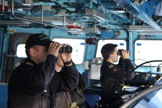 Vaktsjef og assisterende vaktsjef på broen på KNM Roald Amundsen. Kikker ut i horisonten.