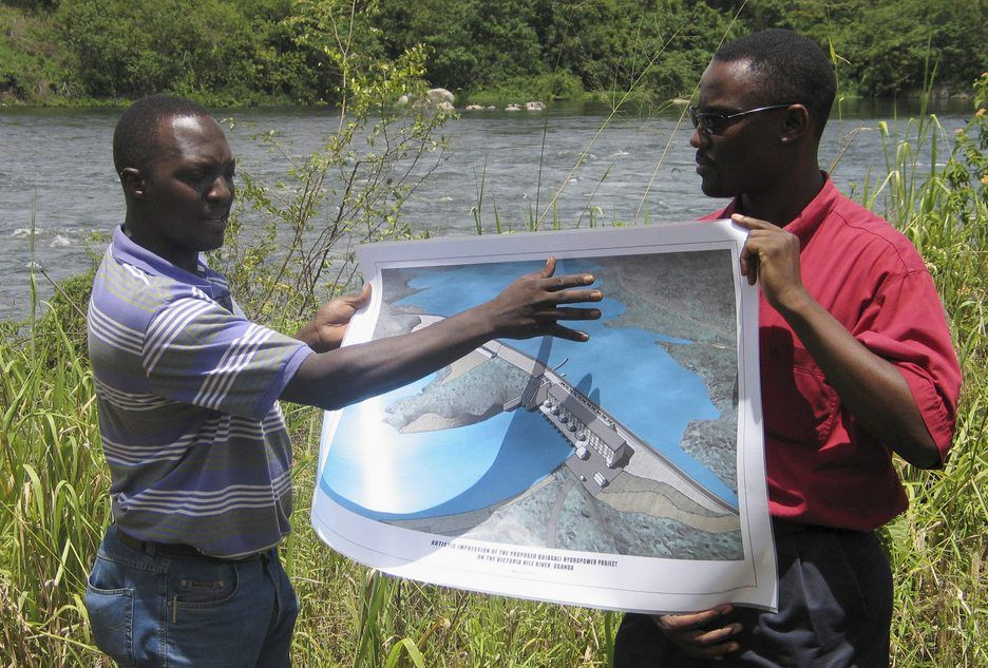 MISTET STØTTEN: Representanter for energiselskapet viser frem en illustrasjon av det planlagte vannkraftverket i Bujagali i Uganda i juli 2007. De norske selskapene Veidekke og Norplan deltok i første fase av utbyggingen, men nå har Verdensbanken trukket sin støtte til prosjektet på grunn av korrupsjonsanklager. Arkivfoto: Reuters/Scanpix
