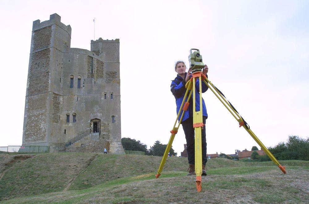 GJENSKAPER: Arkeologiske forskere brukte eksakte teodolitter for å måle og registrere vinkler og avstander i bygnings- og vollgravsystemet rundt det eldgamle Orford Castle i England. Under de gressbevokste haugene ligger restene av forsvarsverk og bygninger. Dette skal gjenskapes i 3D og store modeller. FOTO: LPS