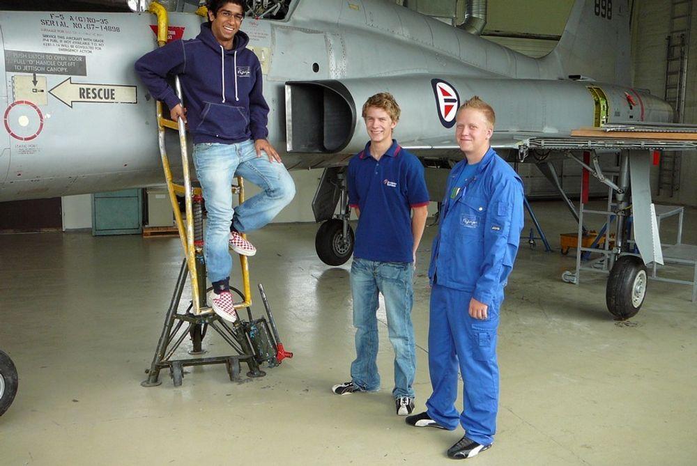 """TRE GLADE: De tre elevene (f.v.) Leroy Lobo, Joachim Stadum og Tor-Rrik Støvland.fra Flylinja på Skedsmo videregående skole gjorde det skarpt ved en engelsk, internasjonal sommerskole for slike studenter. Skolen har 72 slike elever. Flylinja har egen """"hangar"""" med bl. et utrangert F-5 kampfly som undervisningsobjekt (bak)."""