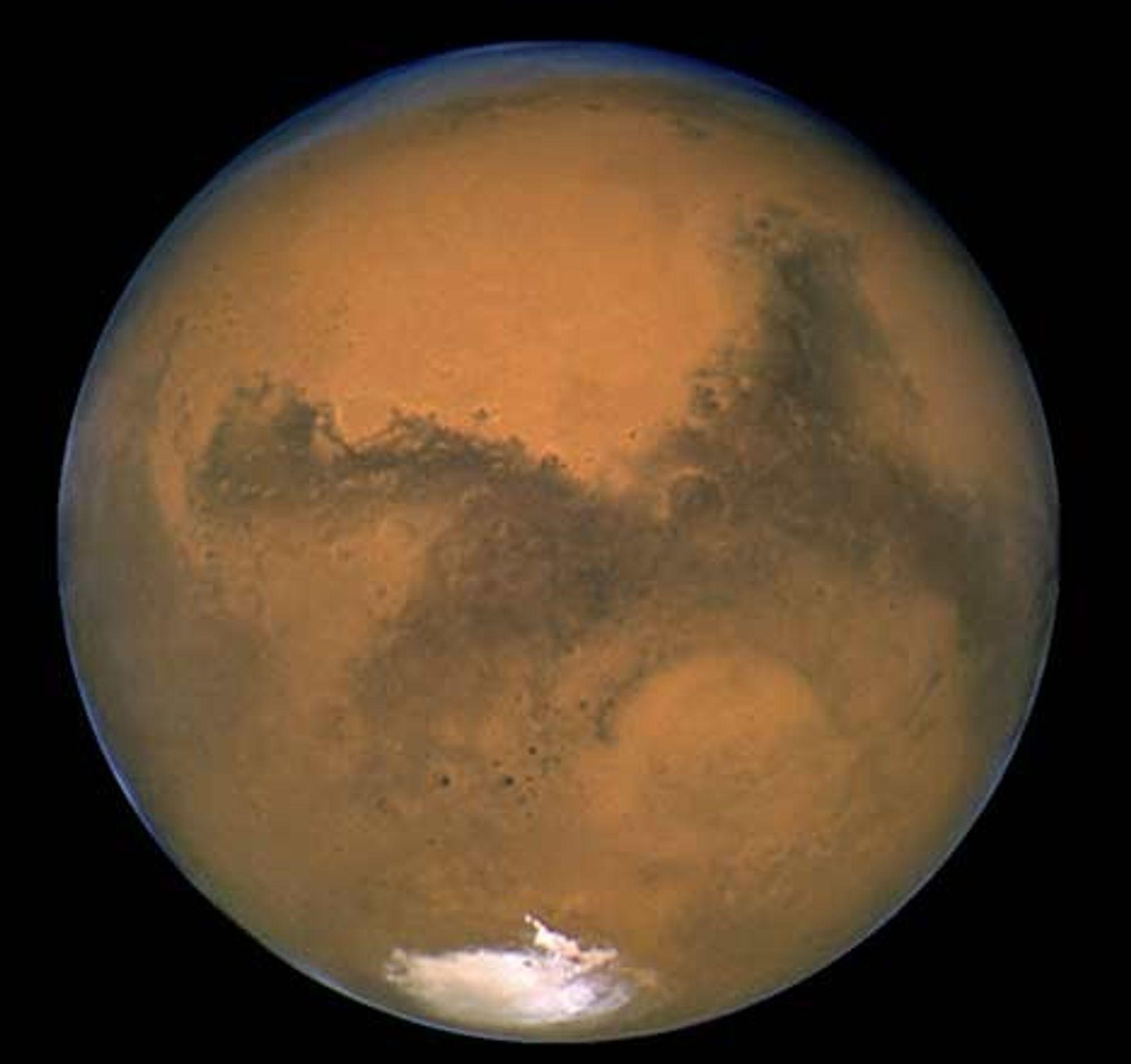 mars.jpg: Den røde planet Mars er fortsatt synlig på nattehimmelen. Der oppe er nå to robotbiler i gang med å lete etter vann. Foto: NASA/STScI