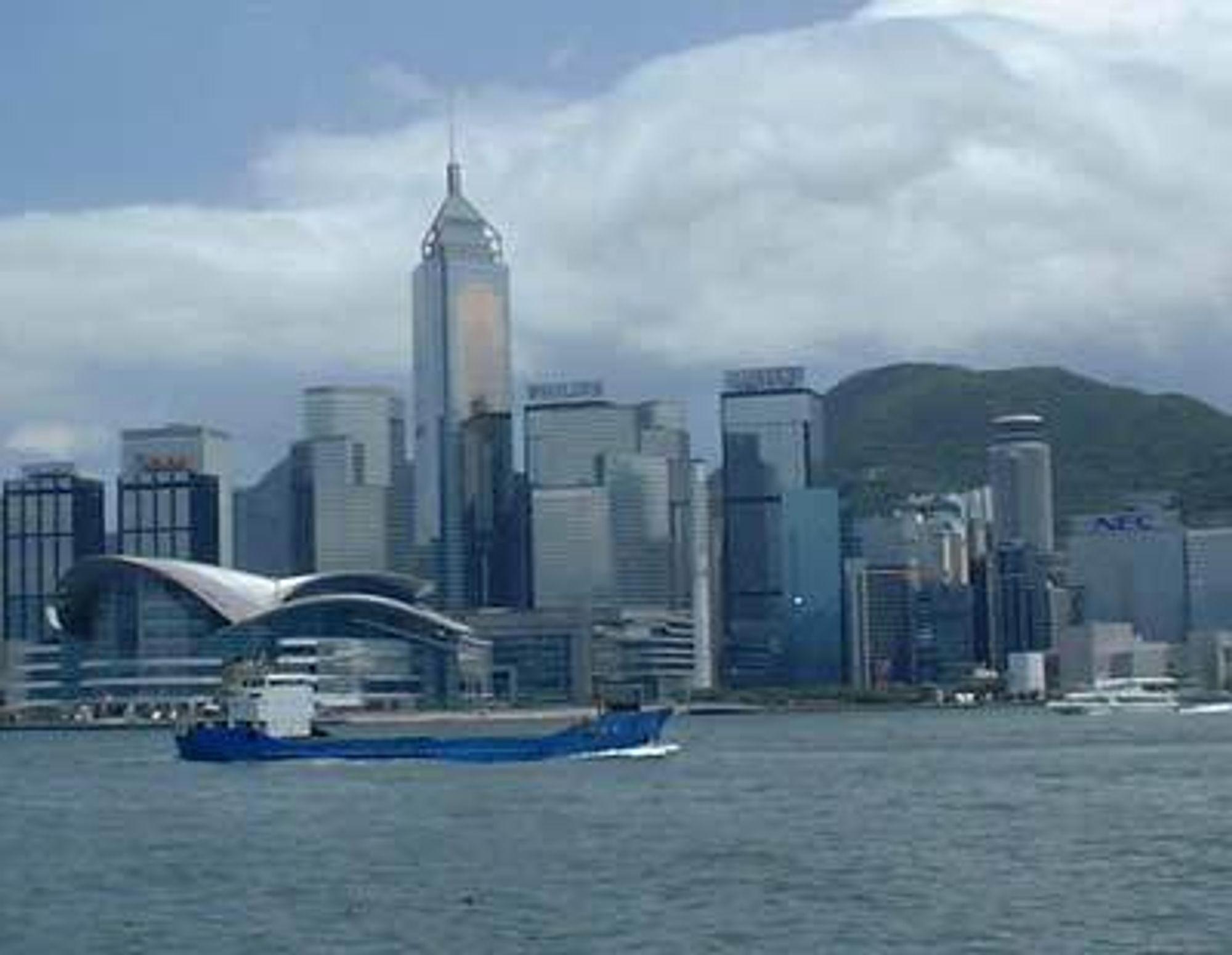 Hong Kong, kina. Skyskrapere sett fra sjøen, med lasteskip foran