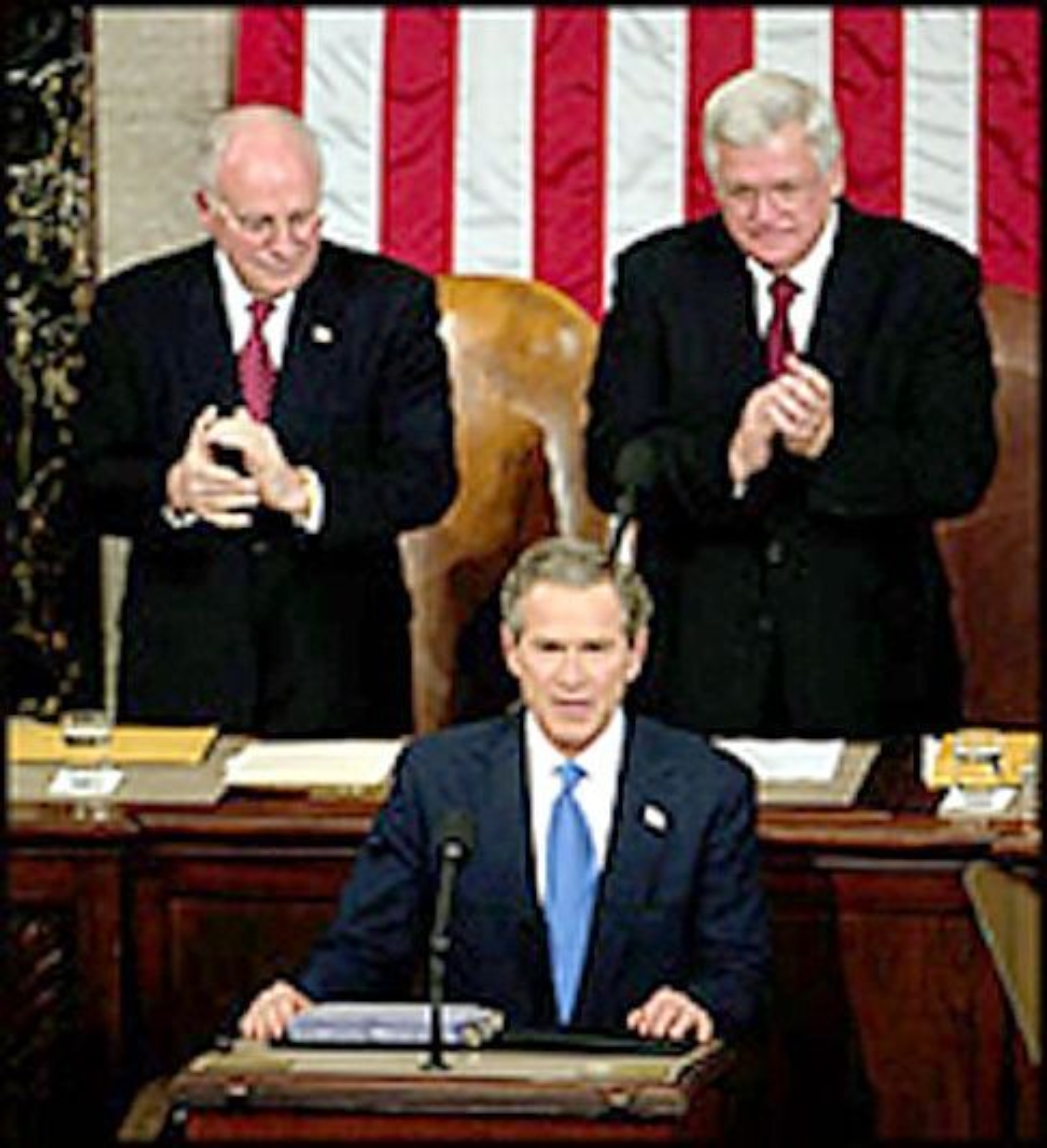 President George W. Bush på talerstolen med visepresident Dick Cheney ivrig applaudrende til venstre bak ham.