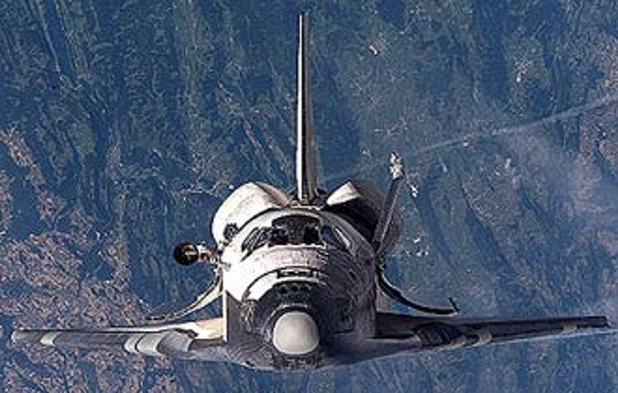 """Discovery fotografert fra ISS - Den internasjonale romstasjonen - i forrige uke under den såkalte """"roll over""""-manøvren. Mannskapet på ISS fotograferte alle deler av fergens varmeskjold for å avdekke eventuelle fatale skader."""