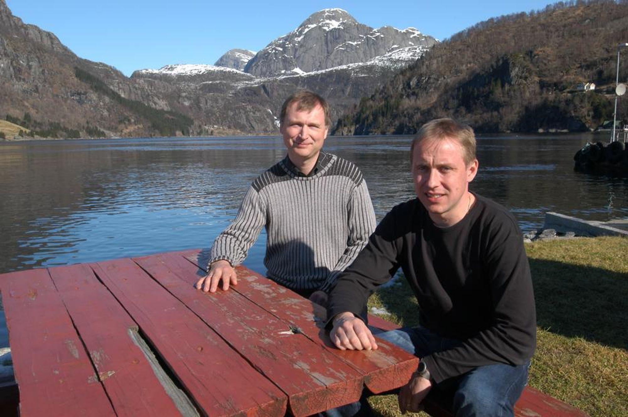 KVALITET: Det er kvalitet å bo i distrikts-Norge mener Ove Mykebust og Johnny Hausbakk. Nå håper de snart at det vil bli bygget bru over fjorden i bakgrunnen.