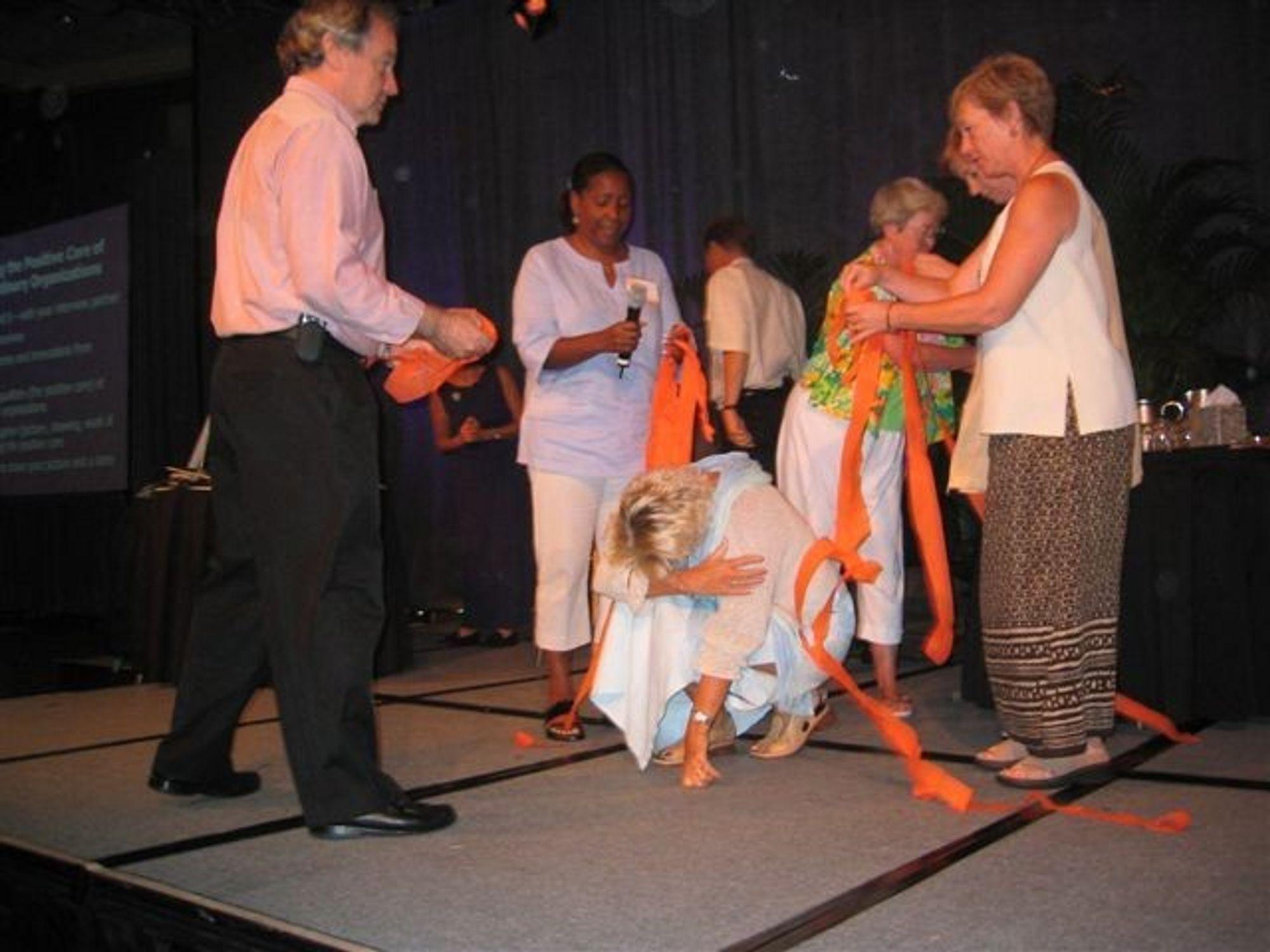 Ruth Nesje i midten med resten av sin gruppe på podiet i Miami under en AI-konferanse i fjor høst.