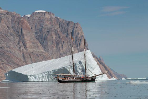 Seilbåten Opal med isfjell i bakgrunnen. Med batteridrift vil North Sailing slippe å bruke motor i sårbare, arktiske strøk.
