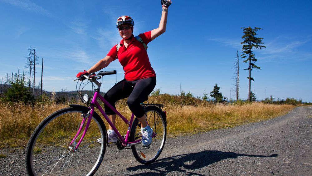 Happy woman riding a bike in a countryside