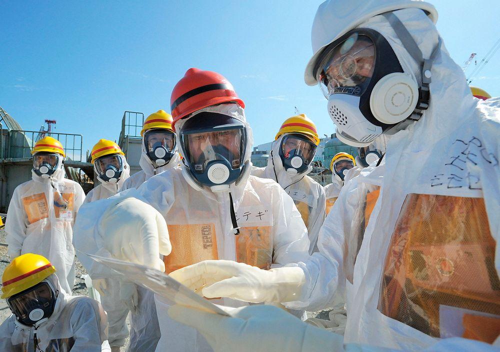 Japans minister for økonomi, handel og industri, Toshimitsu Motegi (i midten), besøker det ulykkesrammede atomkraftverket Fukushima Daiichi ikledd beskyttelsesklær og maske. Målinger har den siste tida avslørt store lekkasjer av radioaktivitet ved kraftverket.