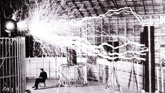 Nikola Tesla i laboratoriet i Colorado Springs, desember 1899. Bildet er dobbeleksponert - de elektriske strålene er tatt i et mørkt rom, mens Tesla og rommet er eksponert i etterkant.