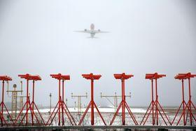Et Boeing 787-8 fra Norwegian tar av fra Oslo lufthavn. De røde antennene utgjør retningsfyret (localizer).
