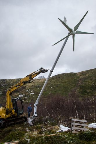 Her monteres en vindmølle helt øverst i terrenget over huset – tilsammen leverer sol og vind strøm som lagres i to truckbatterier.