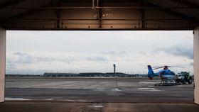 Et av helikoptertjenestens to EC135 T2+ skyves inn i hangaren ved hjelp av den politimerkedede traktoren.