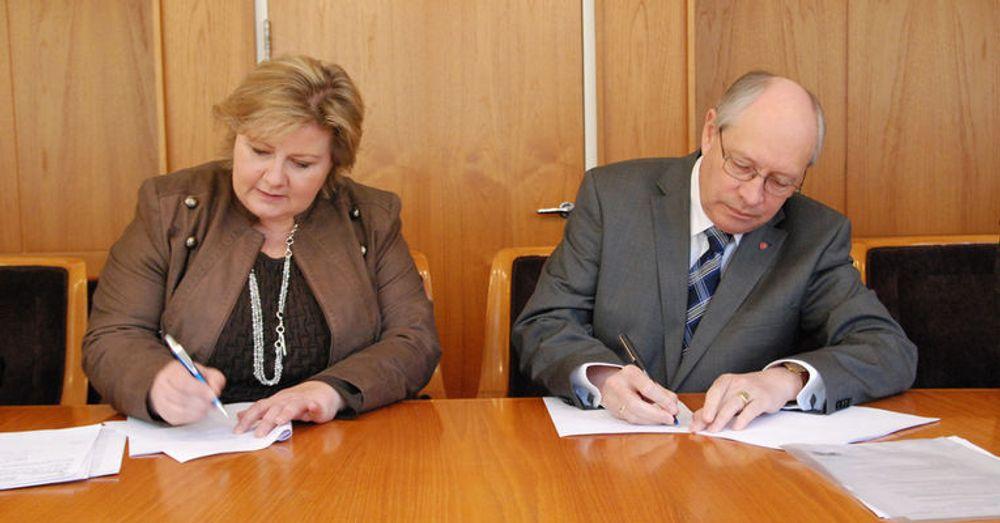 Høyres Erna Solberg og Arbeiderpartiets Martin Kolberg undertegner partienes avtale om DLD.