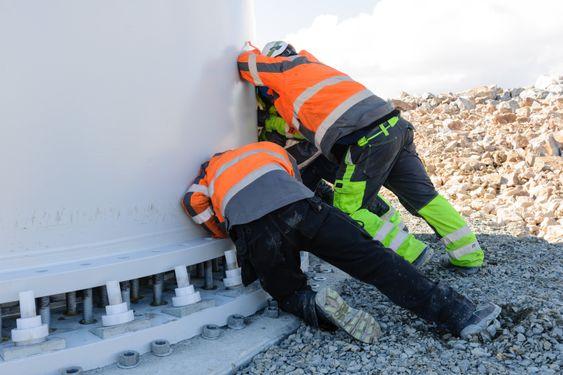 Statkraft regner med at totalt 600 mann vil være i arbeid i den mest intensive anleggsfasen. Her skyver to menn et tårn på plass i Raggovidda vindpark.