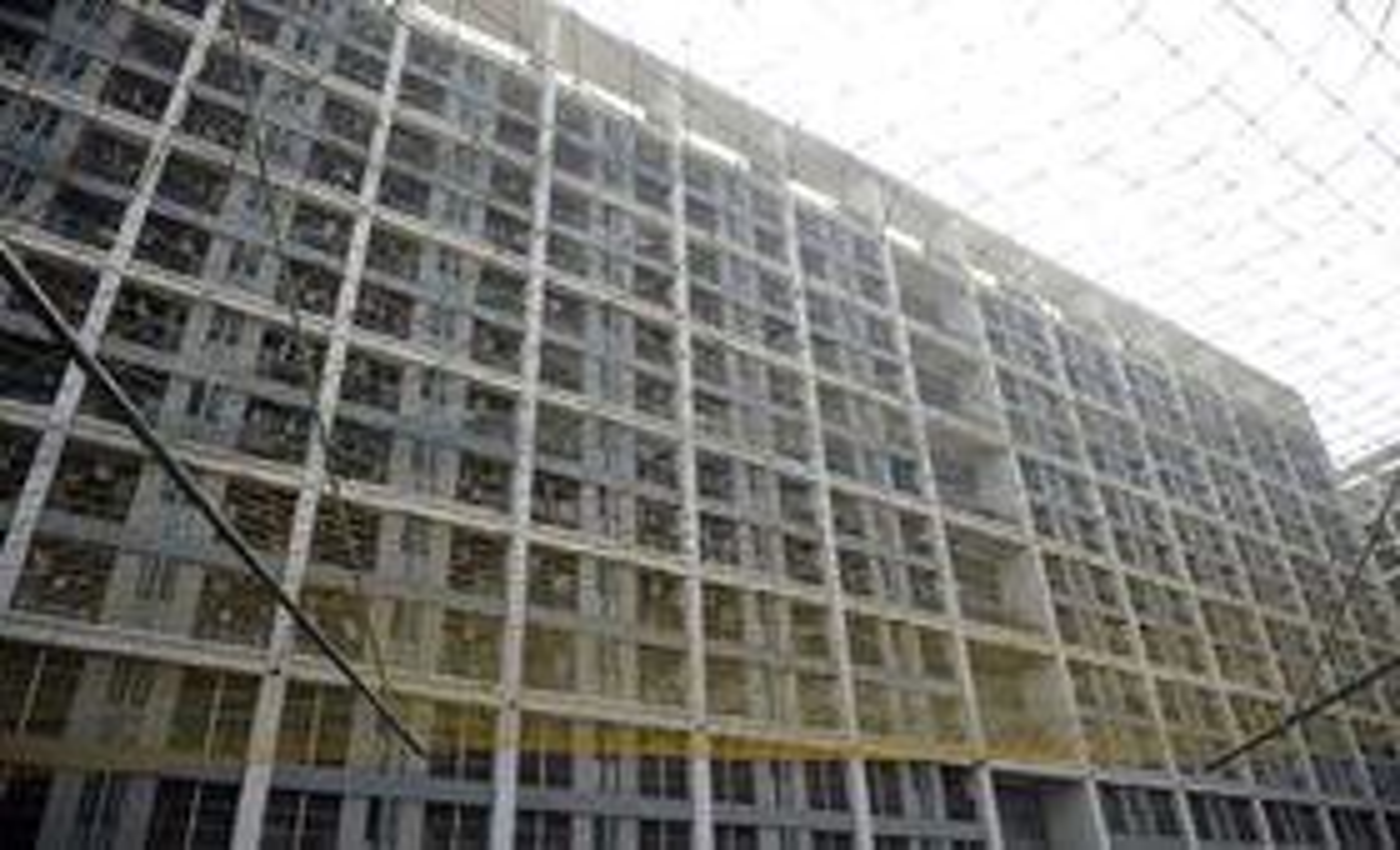 Sikkerhetsnettene Foxconn har hengt opp for å hindre fortvilte ansatte fra å hoppe i døden preger fortsatt fasaden ved fabrikker og gigantiske sovebrakker, som her i Shenzhen.