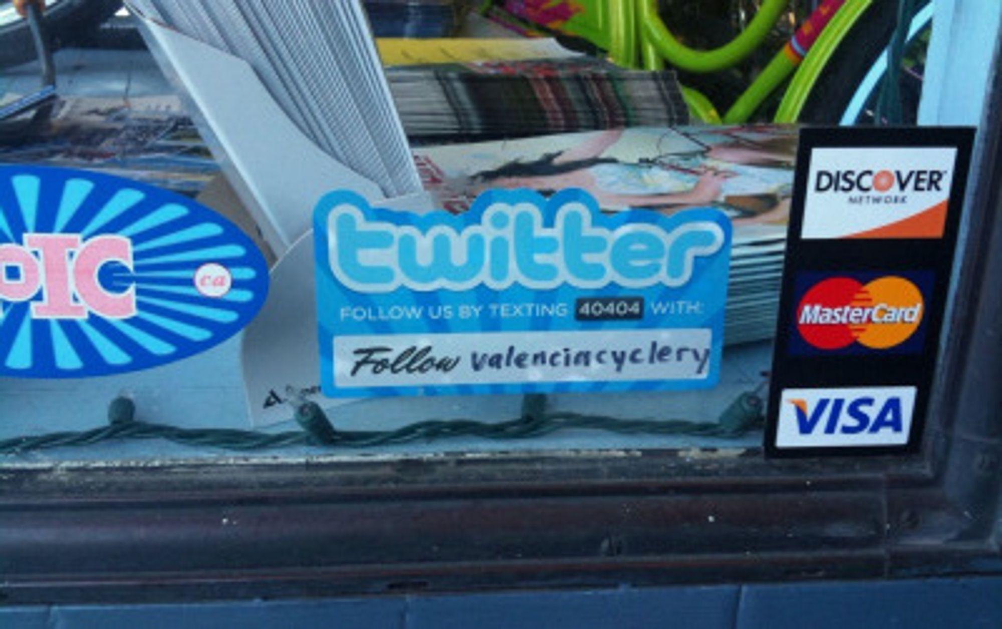 Vitrine fra lokal forretning som tilbyr kundeoppfølging via Twitter på SMS.