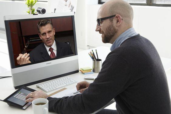 Videokonferanser betjenes med Intouch-enheten (her med venstre hånd). Siden skjermen også fungerer som pc-skjerm, kludrer ikke EX90 det til på pulten.