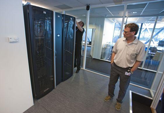 Datarommet bak møterommet i HPs «Enterprise Technology Center» innholder to rack med bladservere og lagring. Mellom rackene er et smalere skap: kjølemodulen. Det lysende feltet midt på kjølemodulen viser driftstemperaturen. Gaute Ledang mekker, Jan Fredrik Gunvaldsen står foran.