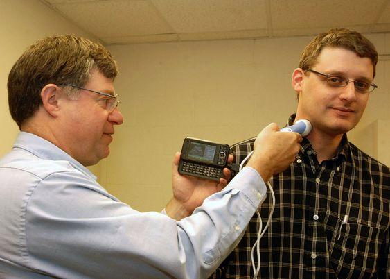 William D. Richard (til venstre) undersøker halspulsåren til David Zar med det laveffekts ultralydutstyret de to har laget. Foto: David Kilper/WUSTL Photo