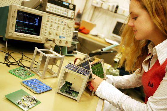 Student ved NTNU bruker et oscilloskop i  arbeid med minisatellitt.