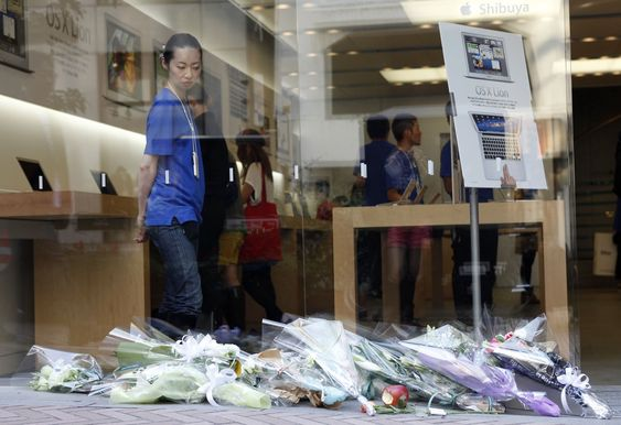 Folk legger ned blomster utenfor Apple Stores verden over. Her fra en av butikkene i Tokyo.