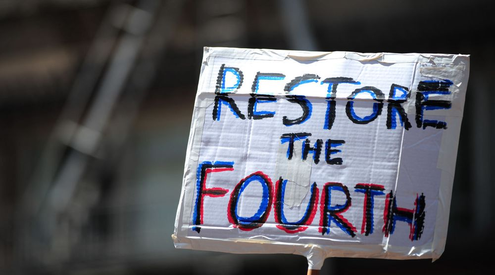 A protester holds a sign asking to restore the fourth after recent information has unearthed a web of NSA spy programs