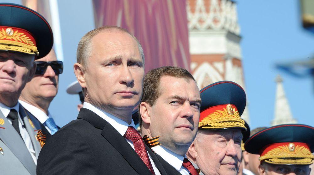 Russlands president Vladimir Putin og statsminister Dmitry Medvedev bivåner en militærparade på Den røde plass tidligere i år.