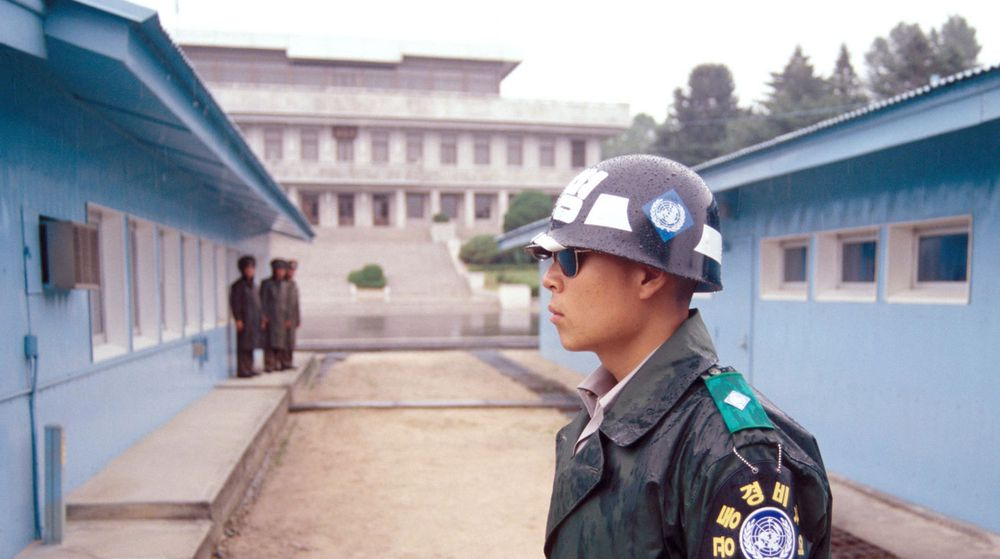 En sørkoreansk grensevakt med steinansikt og mørke solbriller står i full beredskap i DMZ-zonen. De blå husene på bildet markerer det faktiske skillet mellom Nord-Korea og Sør-Korea.