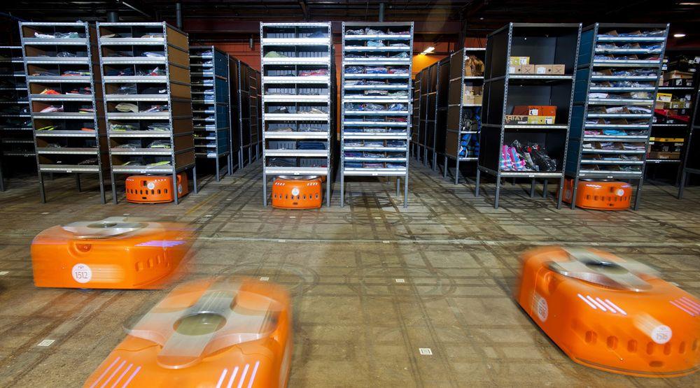 Kiva-robotene er de lave oransje maskinene. De kjører under lagerhyller fulle av varer, og løfter en hel hylle om gangen. Bildet er fra lageret til Acumen Brands. Amazon kjøpte Kiva for over halvannet år siden, og er i gang med å effektivisere sine egne lagre.