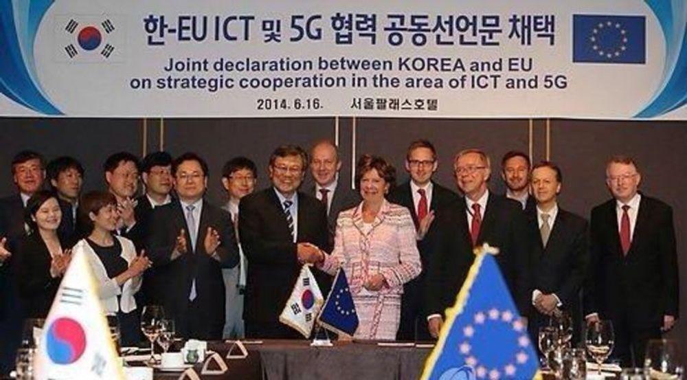 Mun-Kee Choi og Neelie Kroes gratulerer hverandre etter å ha undertegnet en samarbeidsavtale om utvikling av 5G mellom Sør-Korea og EU.